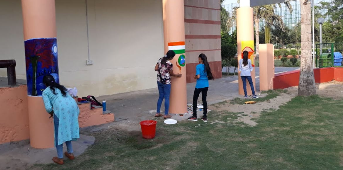Volunteers carry out artworks on walls of Noida Stadium