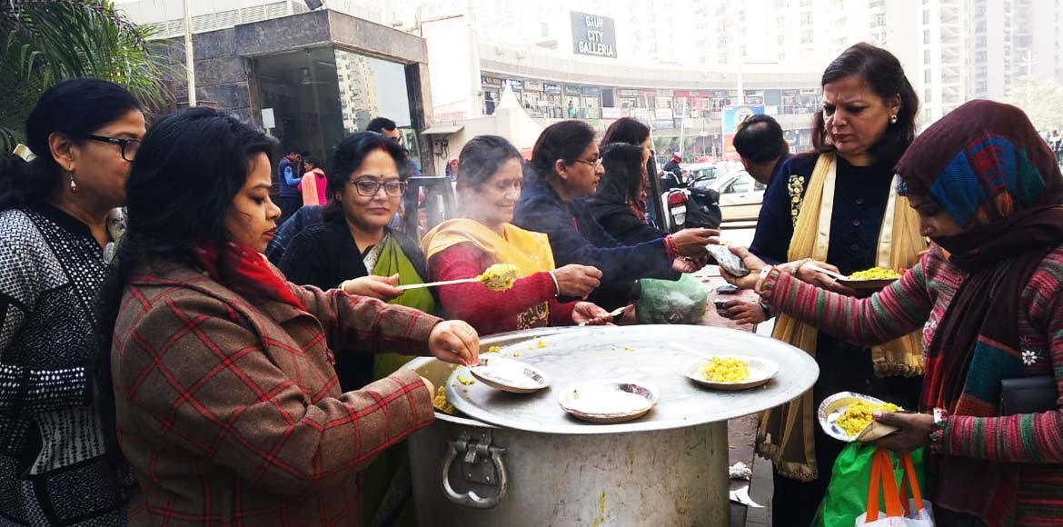 Gaur City-2 women cook and feed the needy on Sankr