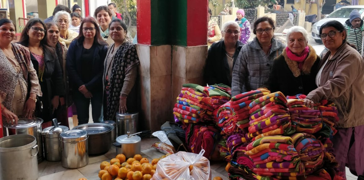 Female residents distribute blankets to leprosy affected people