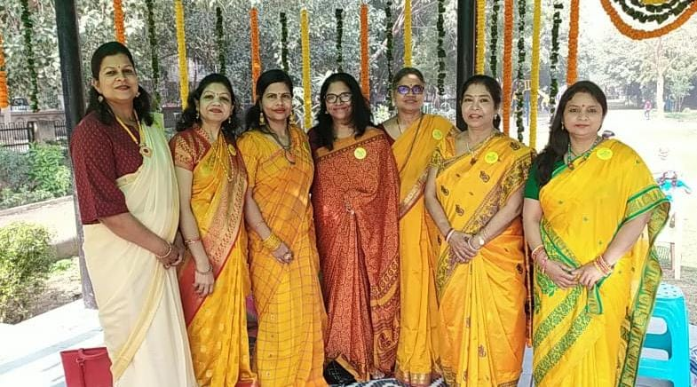 Women in traditional yellow attire posing for a group photograph at Sector 6 park